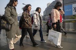 中国ブランドの袋を持って歩く女性。今年はどんな言葉が流行するか(Bloomberg)
