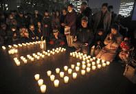 神戸から分灯した「希望の灯り」をキャンドルにともし、手を合わせる人たち=東京都千代田区の日比谷公園で2019年1月17日午後5時46分、佐々木順一撮影