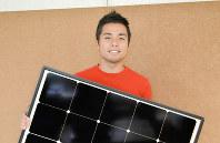 太陽光パネルを掲げる高濱宏至さん=相模原市緑区で2018年10月16日、山衛守剛撮影