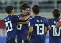 アジア杯【日本・ウズベキスタン】豪快なミドルシュートを決めて逆転、チームメートから祝福される塩谷(中央)=2018年1月17日 UAE・アルアインのハリファインターナショナルスタジアムで、AP