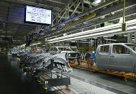 In this March 19, 2018, file photo truck chassis roll down an assembly line at Nissan's Canton, Miss., assembly plant. (AP Photo/Rogelio V. Solis)