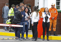 Family members of victims of a bombing gather outside the entrance to the General Santander police academy where the bombing took place in Bogota, Colombia, on Jan. 17, 2019. (AP Photo/John Wilson Vizcaino)