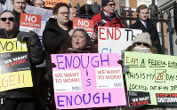 U.S. Internal Revenue Service employees display placards during a rally by federal employees and supporters in front of the Statehouse in Boston, Massachusetts, on Jan. 17, 2019. (AP Photo/Steven Senne)