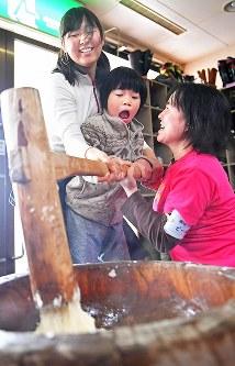 ボランティアらと餅つきをする女の子=新潟県南魚沼市の八海山麓スキー場で2019年1月5日、渡部直樹撮影