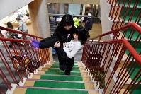 抱きかかえられて階段を上がる女の子=新潟県南魚沼市の八海山麓スキー場で2019年1月5日、渡部直樹撮影