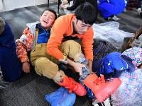 ボランティアに防寒着を着せてもらう男の子。雪でぬれないよう、ビニールやオーバーシューズで足を覆う=新潟県南魚沼市の八海山麓スキー場で2019年1月4日、渡部直樹撮影
