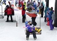 抱きかかえられてリフトに乗るキャンプ男の子=新潟県南魚沼市の八海山麓スキー場で2019年1月5日、渡部直樹撮影