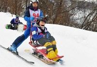 ソリに乗ってゲレンデを滑る参加者=新潟県南魚沼市の八海山麓スキー場で2019年1月5日、渡部直樹撮影