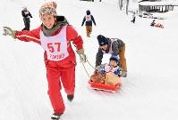 ボランティアにそりを引いてもらい、笑顔があふれる参加者の男の子=新潟県南魚沼市の八海山麓スキー場で2019年1月6日、渡部直樹撮影