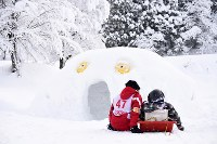 保護者やボランティアの手でつくられたかまくら。そばでは座って話をする参加者も=新潟県南魚沼市の八海山麓スキー場で2019年1月6日、渡部直樹撮影