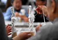 軟らかく延びる粘土の感触を楽しみながら作品作りに取り組む参加者ら=京都市上京区で、小松雄介撮影