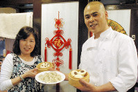 Emiko Onaka, left, and one of the cooks at her Chinese restaurant, stand before a New Year's decoration that says