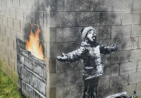In this file photo dated Dec, 20, 2018, showing an artwork by Banksy on the side of a garage depicts a child dressed for snow playing in the falling ash and smoke from a skip fire, in Port Talbot, Wales.. (Ben Birchall/PA FILE via AP)