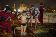 Russian Emergency Situations employees help a boy to bath in the icy water on Epiphany at the Church of the Holy Trinity in Ostankino near TV Tower in Moscow, Russia, on Jan. 18, 2019. (AP Photo/Alexander Zemlianichenko)
