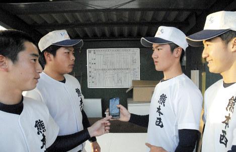 天気情報を確認しながら屋内トレーニングの日程を相談する選手たち