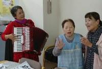 樽本久美さん(左端)の演奏で気持ちよさそうに歌うデイサービスの参加者たち=山口県岩国市で