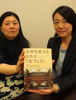 Two Japan International Cooperation Agency (JICA) staff members hold a book that was compiled by the organization on its activities relating to the formulation of laws in developing countries, in Tokyo's Chiyoda Ward, on Dec. 25, 2018. (Mainichi/Akira Iida)