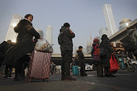 In this Jan. 12, 2019, photo, Chinese people wait to cross a street at the Central Business District in Beijing. China's slowing economy is squeezing the urban workers and entrepreneurs the ruling Communist Party is counting on to help transform this country from a low-wage factory floor into a prosperous consumer market. (AP Photo/Andy Wong)
