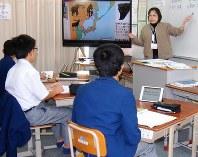 カーテンやカーペットで音を聞こえやすくした教室。生徒はタブレットで教員の話す内容を文字で読める=二条中で