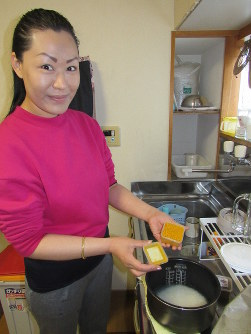 Duptho Choden adds turmeric to a rice cooker before steaming the rice for the dish