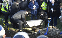 A coffin with the remains of six unidentified Holocaust victims is buried at the United Synagogue's New Cemetery in Bushey, England, on Jan. 20, 2019. (John Stillwell/PA via AP)