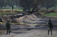 Soldiers guard the site where a gas pipeline exploded two days prior, in the village of Tlahuelilpan, Mexico, on Jan. 20, 2019. (AP Photo/Claudio Cruz)