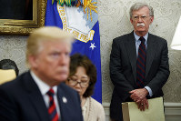 In this May 22, 2018 file photo, U.S. President Donald Trump, left, meets with South Korean President Moon Jae-In in the Oval Office of the White House in Washington, as national security adviser John Bolton, right, watches. (AP Photo/Evan Vucci)