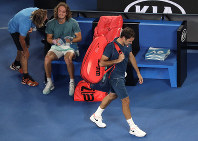 Switzerland's Roger Federer, right, leaves Rod Laver Arena after losing his fourth round match to Greece's Stefanos Tsitsipas at the Australian Open tennis championships in Melbourne, Australia, on Jan. 20, 2019. (AP Photo/Kin Cheung)