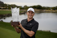 Adam Long holds the trophy on the 18th green after winning the Desert Classic golf tournament on the Stadium Course at PGA West on Jan. 20, 2019, in La Quinta, Calif. (AP Photo/Chris Carlson)