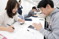 アプリの説明をする芝野さん(左端)と名取さん(左から3人目)と、様子を見守る高野倉さん(同2人目)=2018年12月1日、千葉市美浜区で岡本同世撮影
