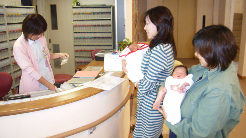 新生児を抱いて退院する女性