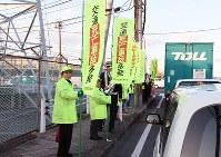のぼりを持ち、ドライバーに安全運転を呼びかける参加者ら=高松市福岡町3で、潟見雄大撮影