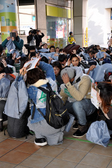 Participants take cover during an earthquake drill at Machida Terminal Plaza in the Tokyo suburban city of Machida on Jan. 21, 2019. (Mainichi/Eimi Igarashi)