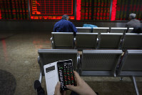 A man checks stock prices through his smartphone at a brokerage house in Beijing, on Jan. 22, 2019. (AP Photo/Andy Wong)