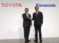 In this Dec. 13, 2017 file photo, Toyota Motor Corporation President Akio Toyoda, left, and Panasonic Corporation President Kazuhiro Tsuga pose for photographers after a joint press conference in Tokyo. (AP Photo/Eugene Hoshiko)