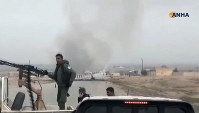 This frame grab from video provided by Hawar News, ANHA, the news agency for the semi-autonomous Kurdish areas in Syria, shows Kurdish fighters standing guard at the site of a suicide attack near the town of Shaddadeh in Syria, on Jan. 21, 2019. (ANHA via AP)