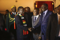 Zimbabwean President Emmerson Mnangagwa, left, is greeted as he arrives at Robert Mugabe International Airport in Harare, Zimbabwe, Monday, Jan. 21, 2019. (AP Photo/Tsvangirayi Mukwazhi)