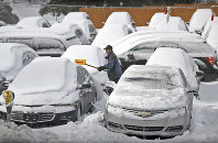 An employee for Hornbeck Chevrolet clears away ice and snow in a frozen parking lot of used vehicles in Forest City, Pennsylvania, on Jan. 21, 2019. (Butch Comegys/The Times-Tribune via AP)