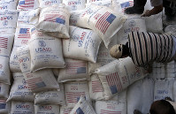 In this June 4, 2008 file photo, Palestinians unload bags of flour donated by the United States Agency for International Development, USAID, at a depot in the West Bank village of Anin near Jenin. (AP Photo/Mohammed Ballas)