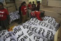 Pakistan volunteers arrange bodies of passengers killed in an accident, in Karachi, Pakistan, on Jan. 22, 2019. (AP Photo/Fareed Khan)