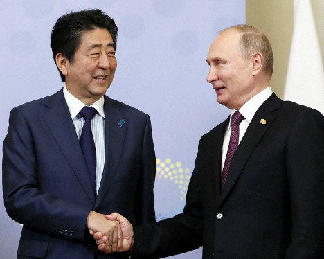 Japanese Prime Minister Shinzo Abe (L) and Russian President Vladimir Putin shake hands ahead of their talks in Buenos Aires on Dec. 1, 2018, on the margins of a Group of 20 summit. (Kyodo)