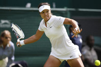 In this June 23, 2014 file photo, Li Na of China plays a return to Paula Kania of Poland during their first round match at the All England Lawn Tennis Championships in Wimbledon, London. (AP Photo/Pavel Golovkin)
