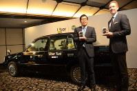 タクシー配信サービスをPRするウーバー日本法人のトム・ホワイト氏(右)と未来都の笹井大義専務=大阪市で2019年1月23日、釣田祐喜撮影