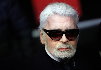 In this Nov. 22, 2018 file photo, Fashion designer Karl Lagerfeld poses during the Champs Elysee Avenue illumination ceremony for the Christmas season, in Paris. (AP Photo/Christophe Ena)