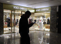 In this Nov. 21, 2018 file photo, a man walks past an outlet of Dolce & Gabbana in Beijing. (AP Photo/Ng Han Guan)