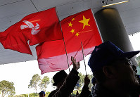 Pro-Beijing protesters raise the Chinese National flag and the Hong Kong flag during a protest outside Legislative building in Hong Kong, on Jan. 23, 2019. (AP Photo/Vincent Yu)