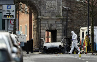 Forensic investigators at the scene of a car bomb blast on Bishop Street in Londonderry, Northern Ireland, on Jan. 20, 2019. (Niall Carson/PA via AP)