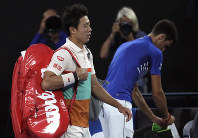 Japan's Kei Nishikori, left, walks from Rod Laver Arena after retiring injured from his quarterfinal against Serbia's Novak Djokovic at the Australian Open tennis championships in Melbourne, Australia, on Jan. 23, 2019. (AP Photo/Mark Schiefelbein)