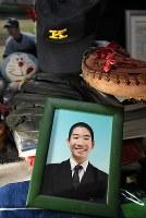 大輔さんの部屋にある笑顔の写真。愛用したグラブや野球部の帽子が置かれていた=東京都港区で2019年1月22日、佐々木順一撮影