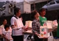 日航ジャンボ機墜落事故現場を訪れた市川正子さん(手前右)。灯籠を手に夕焼け空を見上げた=群馬県上野村で2018年8月11日、佐々木順一撮影